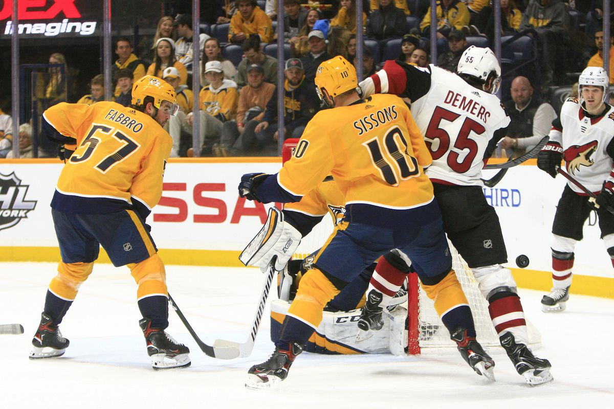 Nashville Predators defenseman Dante Fabbro looks on as winger Colton Sissons and Coyotes defenseman Jason Demers battle for the puck during the NHL game between the Arizona Coyotes and Nashville Predators, held on December 23, 2019, at Bridgestone Arena in Nashville, Tennessee.