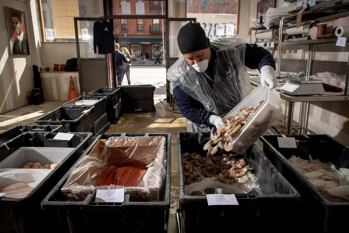 A worker pours shrimp in F. Rozzo's popup seafood shop