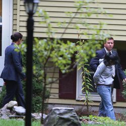 Family member, left, watches as Annie Dookhan, right, is escorted to a cruiser outside her home in Franklin, Mass., Sept. 28, 2012. Dookhan is accused of faking drug results, forging signatures and mixing samples at a state police lab.  State police say Dookhan tested more than 60,000 drug samples involving 34,000 defendants during her nine years at the lab. Defense lawyers and prosecutors are scrambling to figure out how to deal with the fallout.