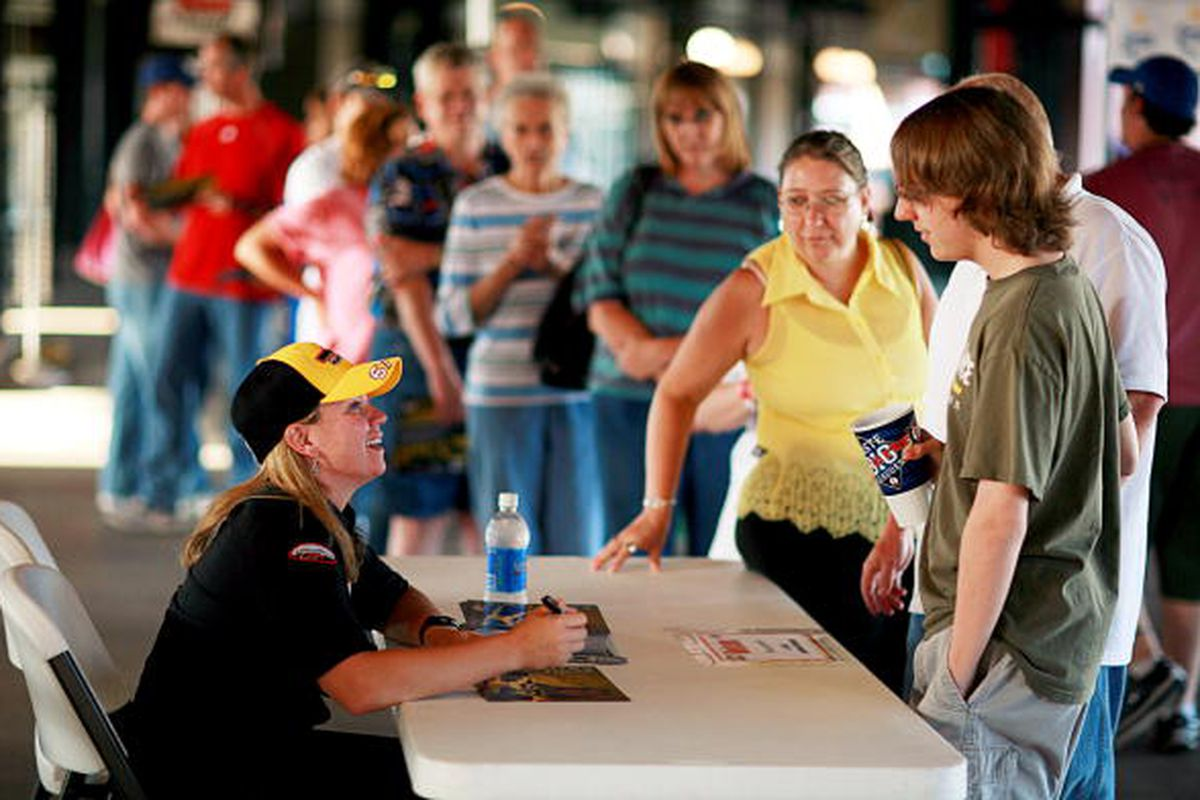 Sarah Fisher signs autographs for fans after throwing out the ceremonial first pitch before an Oklahoma City RedHawks game. Fisher is consistently one of IndyCar's most popular and fan-friendly drivers. (Photo By Tom Pennington/Getty Images)