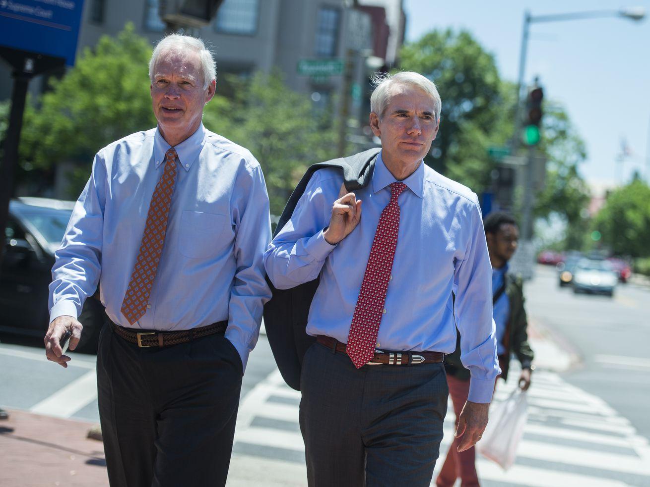 Republican Senators Rob Portman and Ron Johnson walking across an intersection in downtown Washington, DC.