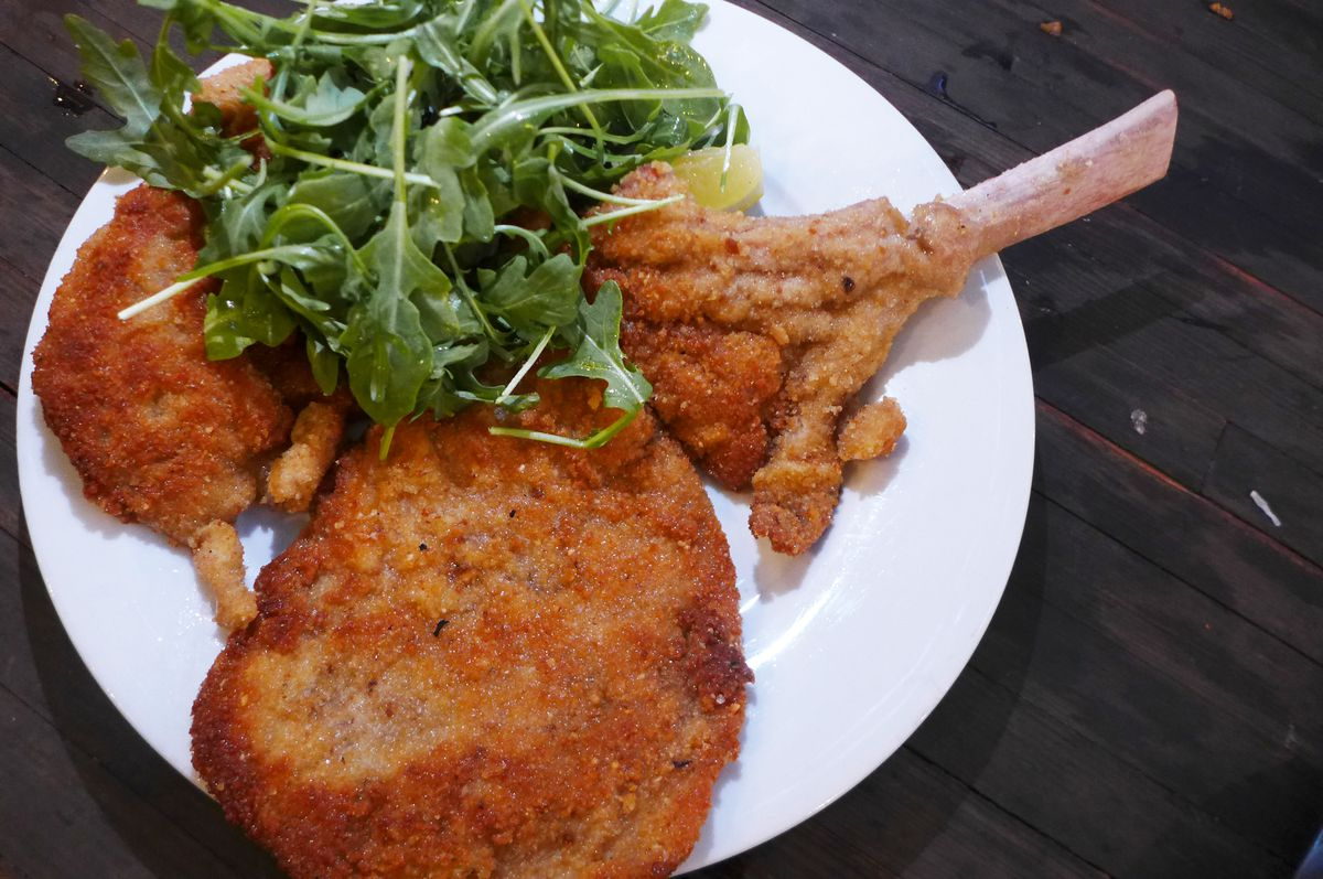 A giant breaded veal chop with a bone sticking out over the edge of the plate.