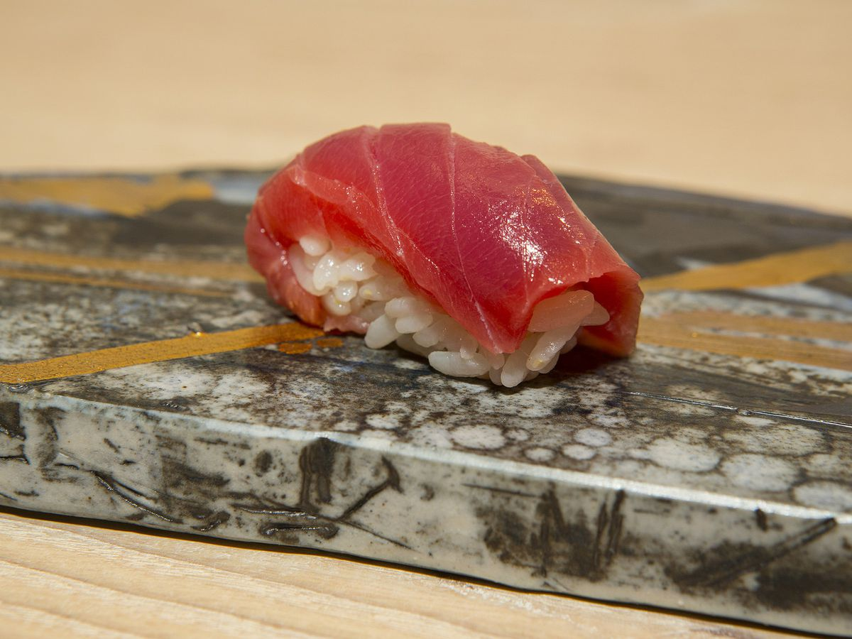 A piece of nigiri with a slice of raw, red fish on a bed of white rice.