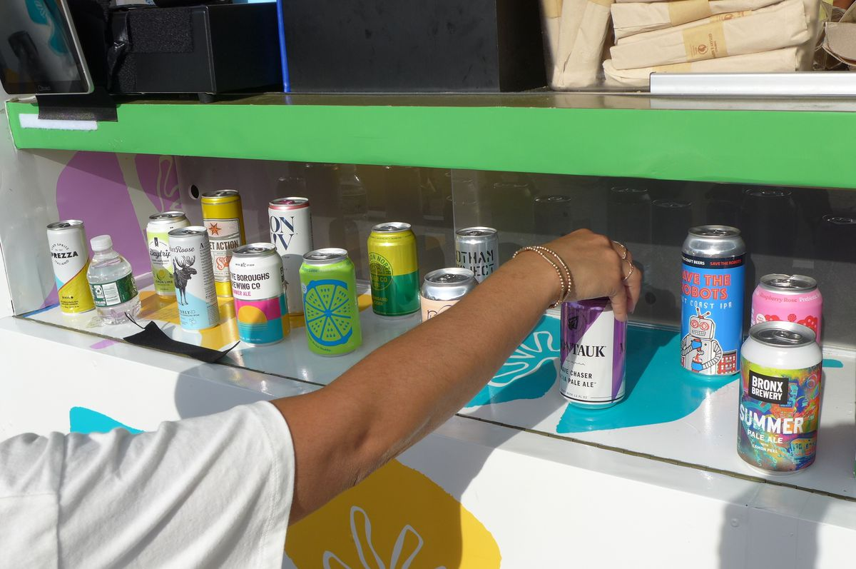An arm reaches out to examine a can of wine from a display of two dozen or so cans.