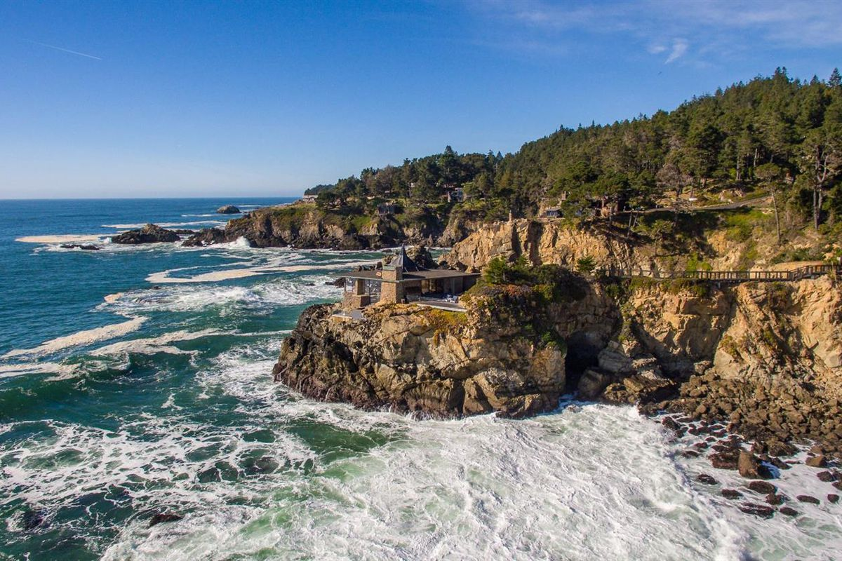 Wide shot of house on cliff jutting out into the ocean.