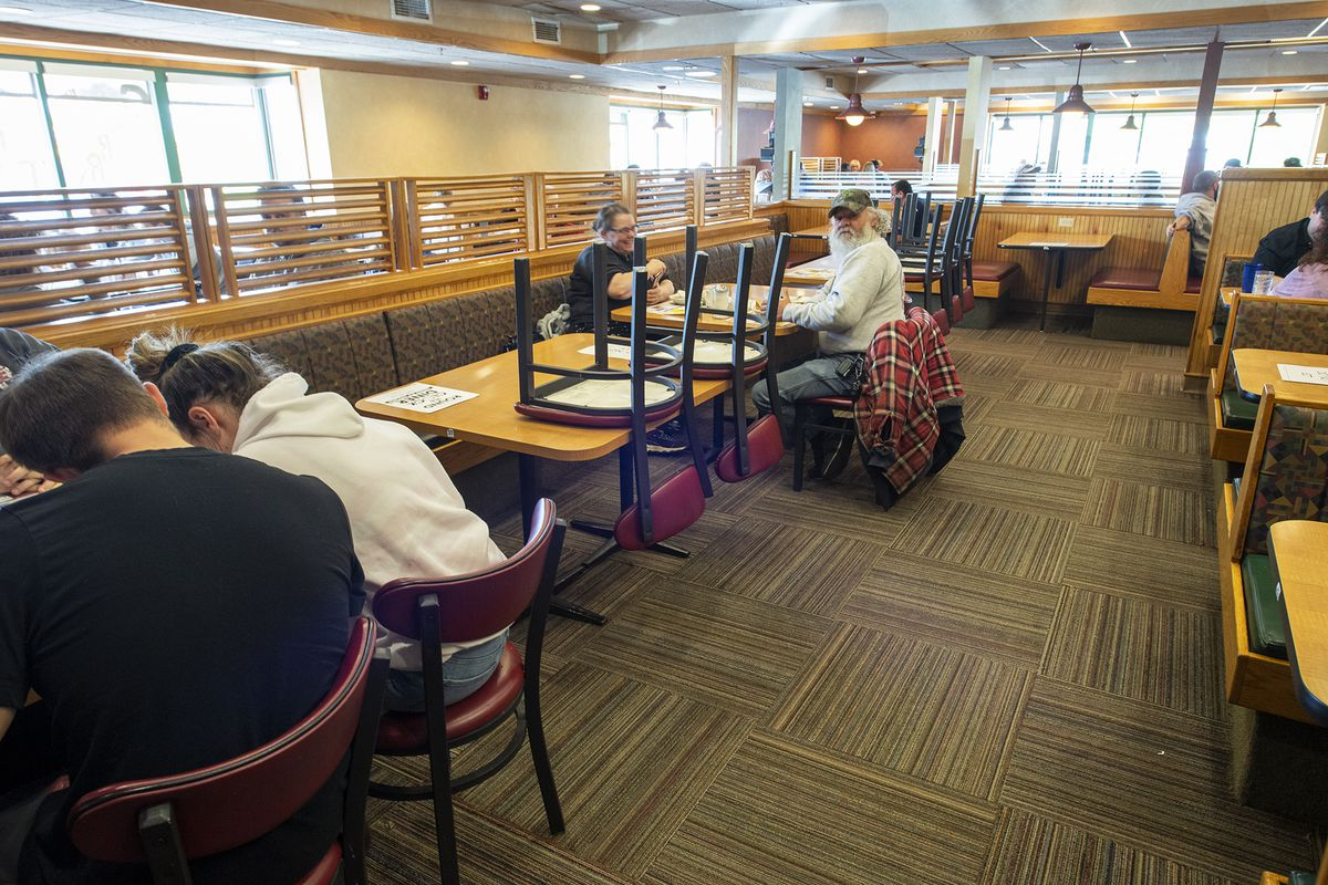 Family groups are separated by tables and signs that tell them to social distance at Around the Clock Diner-East in Springettsbury Township, Pa., Sunday May 10, 2020. The diner opened despite a statewide stay-at-home lockdown in Pennsylvania.