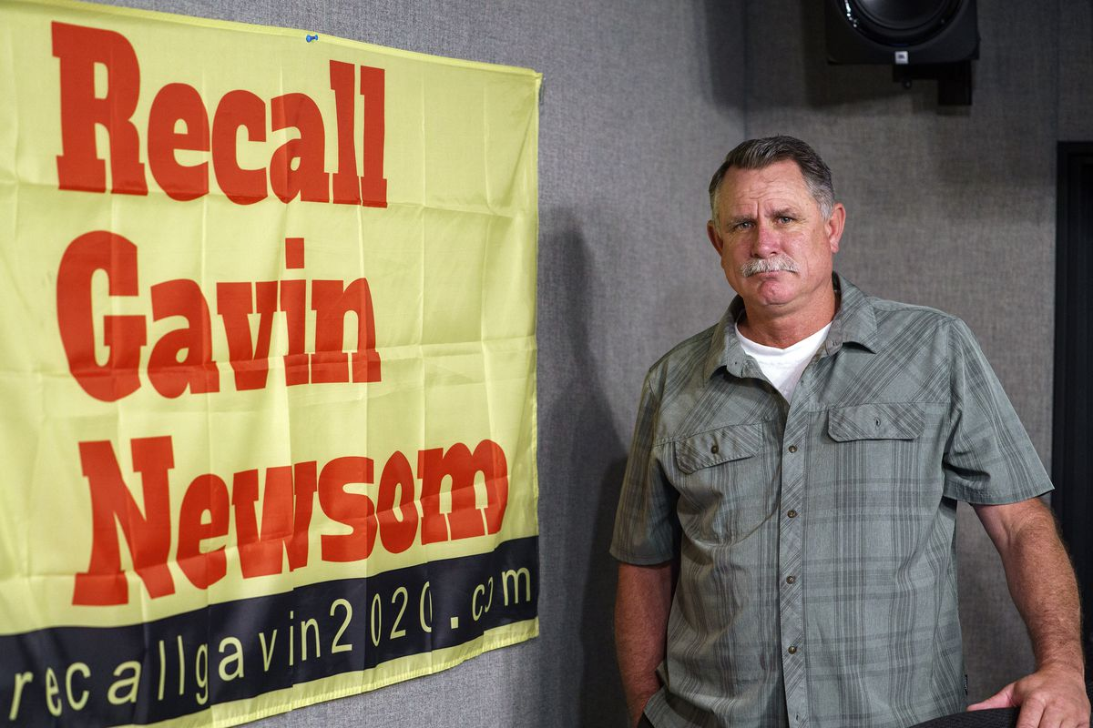 Orrin Heatlie, the main organizer for the Recall of California Gov. Newsom campaign, poses with a banner before recording a radio program at the KABC radio station studio in Culver City, Calif., Saturday, March 27, 2021.