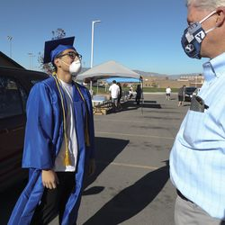 """Francisco Calderon, Pleasant Grove High School student body president, tries on his graduation gear as Principal Steve Stewart watches at the school in Pleasant Grove on Wednesday, April 29, 2020. A graduation """"walk"""" experience will be provided in caps and gowns for each senior during the last 4 days of school.At the end of May, the school will also provide a """"graduation walk"""" experience at the school over four days. Graduates and their immediate family will schedule a time to enter the auditorium, where """"Pomp and Circumstance"""" will be playing and students' names will be read over the school's sound system."""