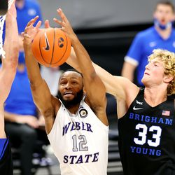 Brigham Young Cougars guard Alex Barcello (13) and Brigham Young Cougars forward Caleb Lohner (33) defend Weber State Wildcats guard Isiah Brown (12) as they play an NCAA basketball game at Vivint Smart Home Arena in Salt Lake City on Wednesday, Dec. 23, 2020.