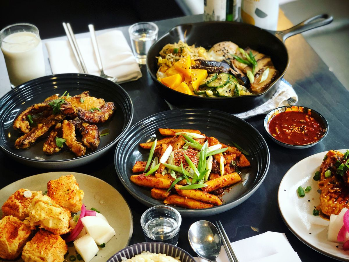 A meal spread on a table from Miss Kim in Ann Arbor on black, white, and stoneware plates and a cast-iron skillet