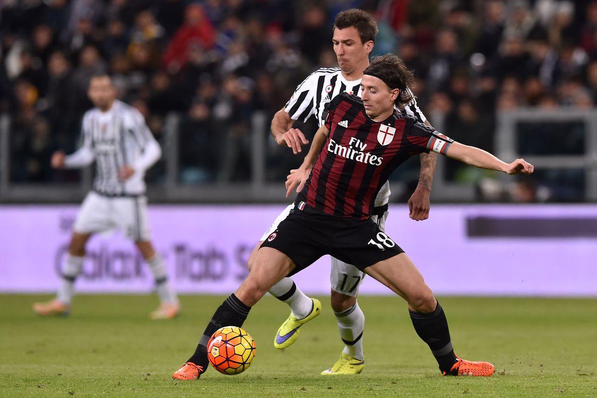Montolivo shields the ball from Juventus's Mario Mandzukic