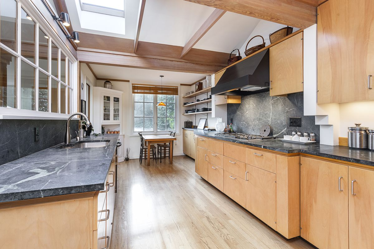 A long kitchen with skylights features wood cabinets, a dark black marbled counter, and wood floors.