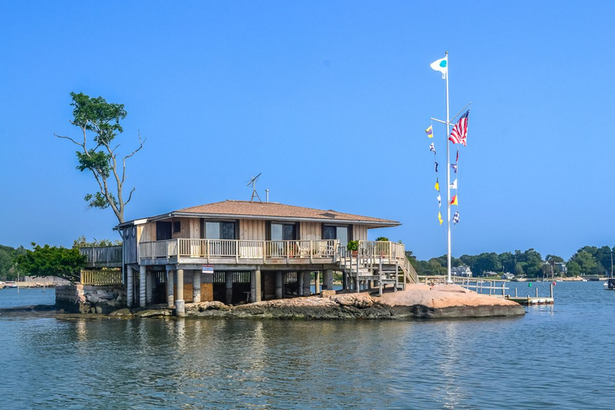 An exterior view of a home on a rocky island, surrounded by water. A flag pole holds many flags.