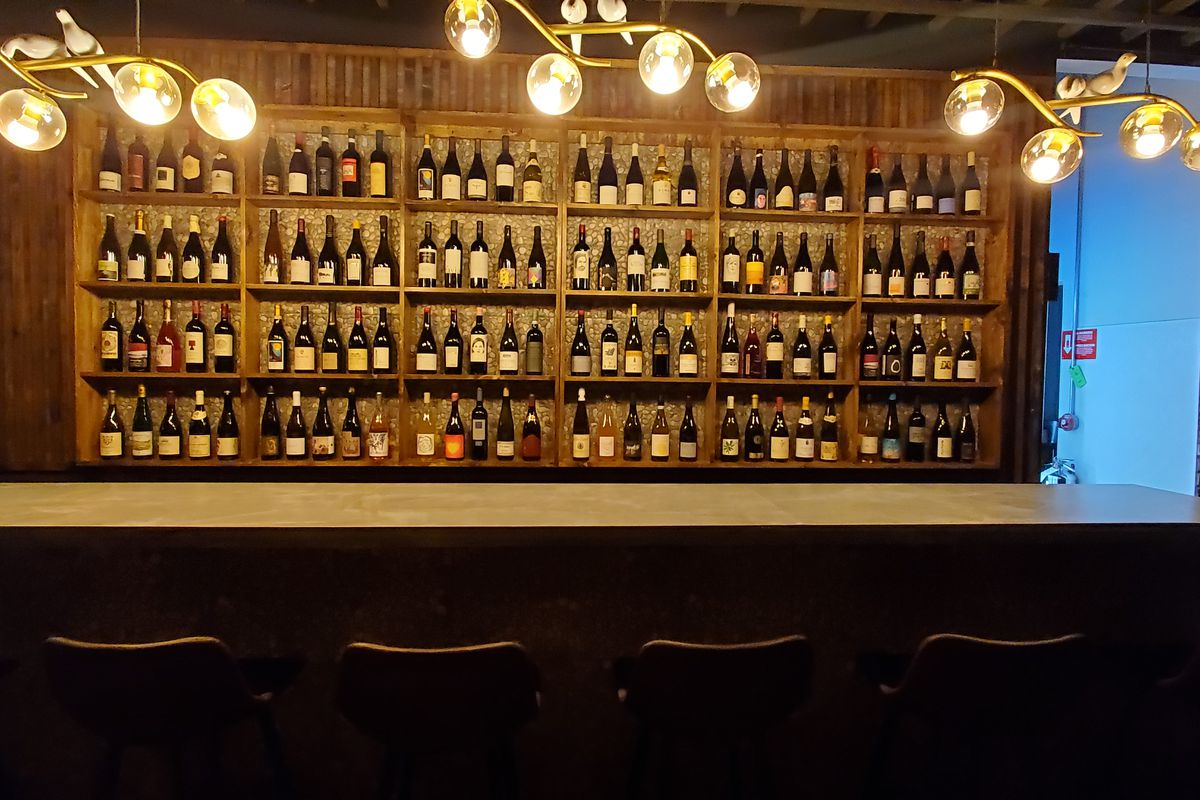 A bar with bottles and bottles and bottles of wine filling the shelves.
