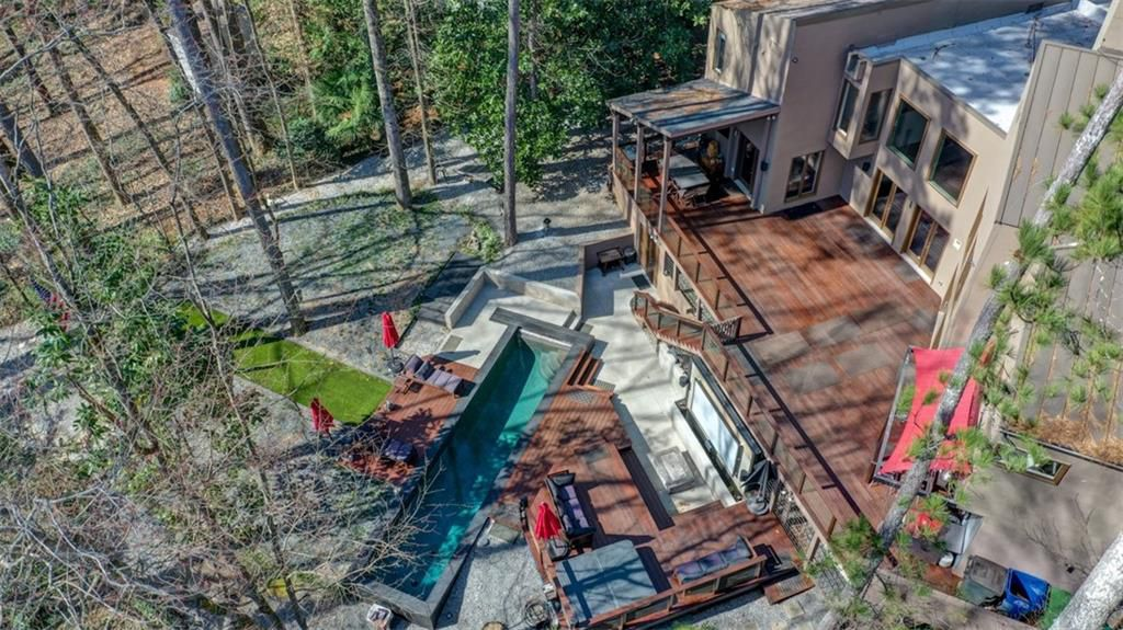The back of a house with small pool and putting green and huge deck.