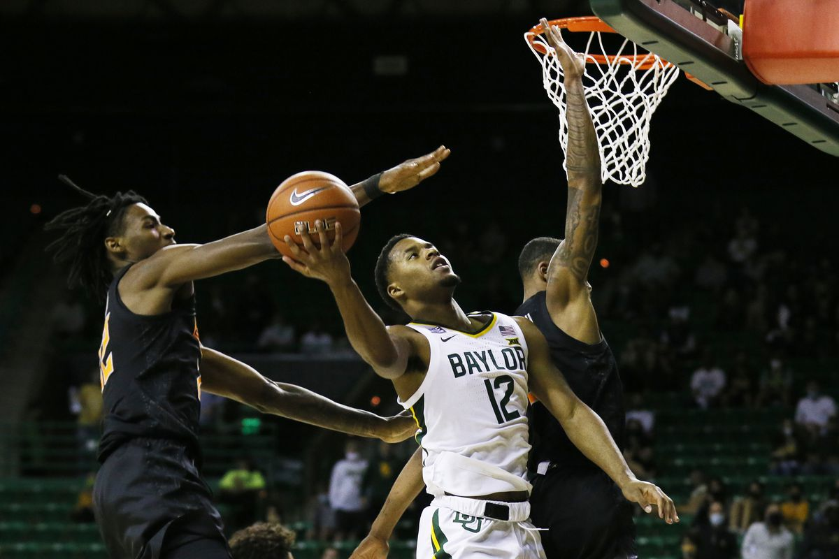 Baylor Bears guard Jared Butler (12) drives the lane on Oklahoma State Cowboys forward Kalib Boone (22) and guard Avery Anderson III (0) during the first half at Ferrell Center.