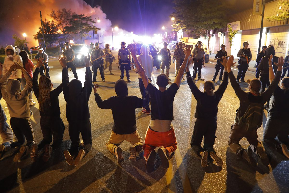 Demonstrators kneel before police Saturday, May 30, 2020, in Minneapolis. Protests continued following the death of George Floyd, who died after being restrained by Minneapolis police officers on Memorial Day.