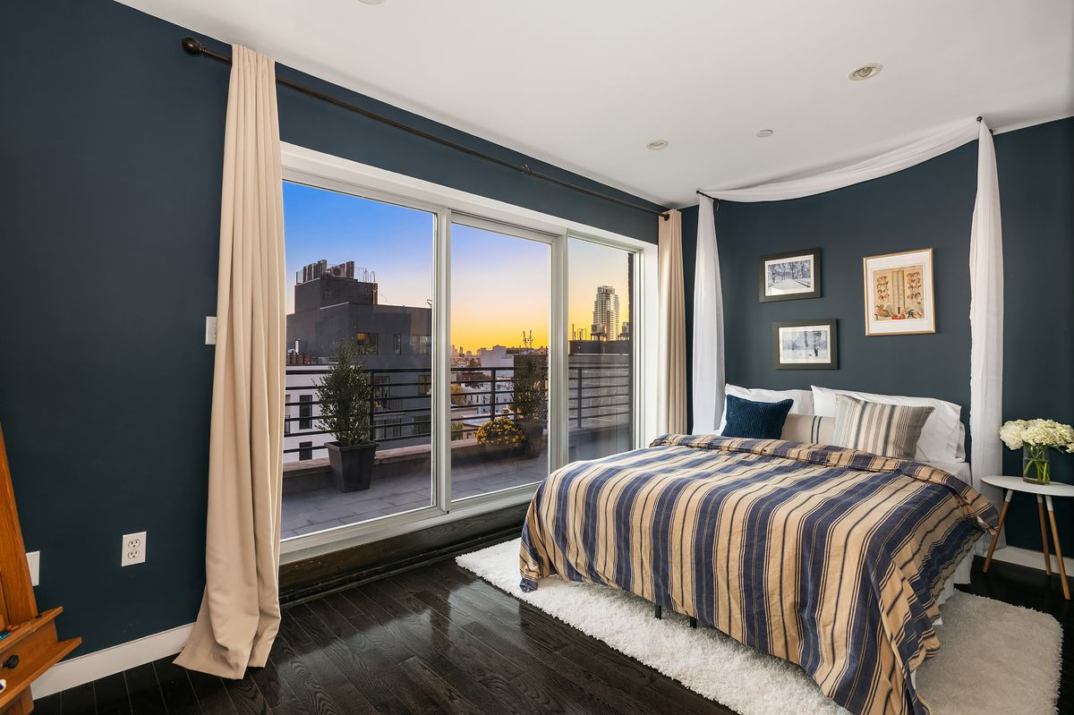 A bedroom with a large bed, dark blue walls, hardwood floors, and a large glass door that leads to a balcony.