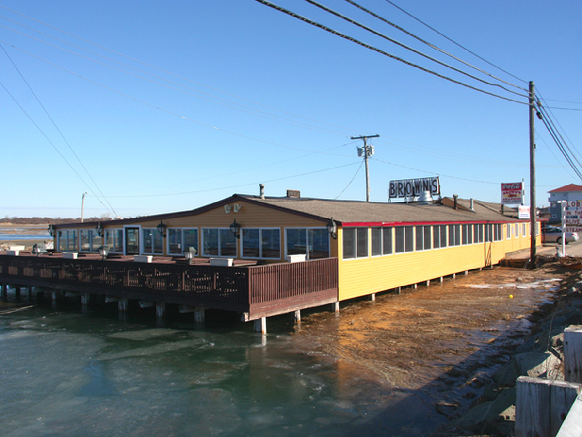 A one-story yellow building with a large wooden deck sits in shallow water.