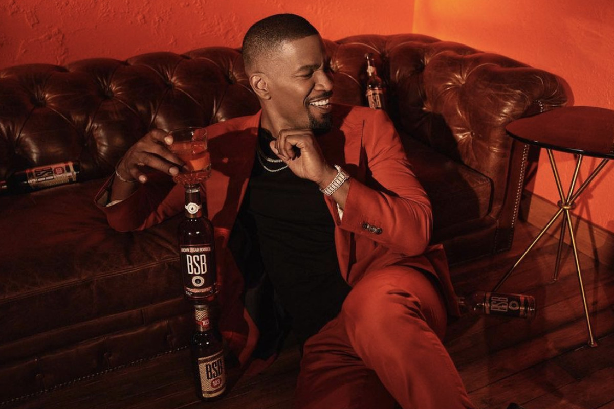 Actor Jamie Foxx in a red suit lounging on a leather couch with a bottle of Brown Sugar Bourbon