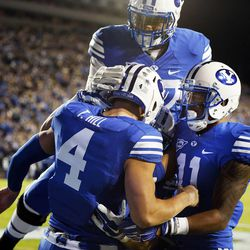 Taysom Hill (4) celebrates with Terenn Houk (11) and De'Ondre Wesley (57) of the Brigham Young University Cougars after scoring a touchdown against Utah State during NCAA football in Provo, Friday, Oct. 3, 2014.