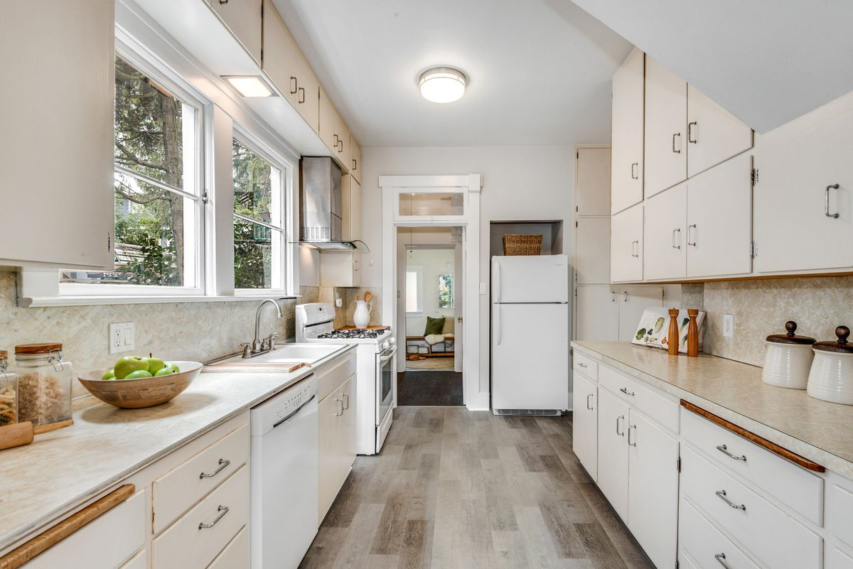 A kitchen has beige and white cabinets and counters and wood floors.