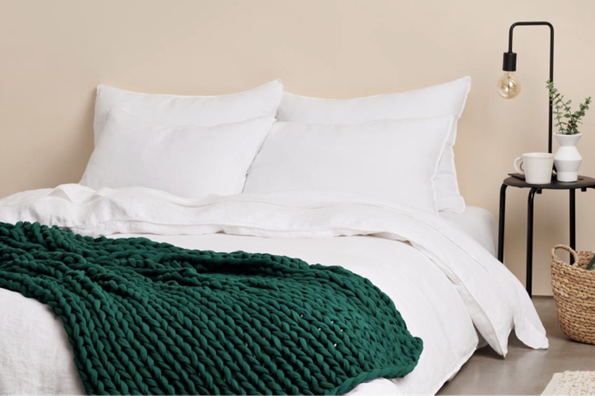 White bedding with green woven blanket.