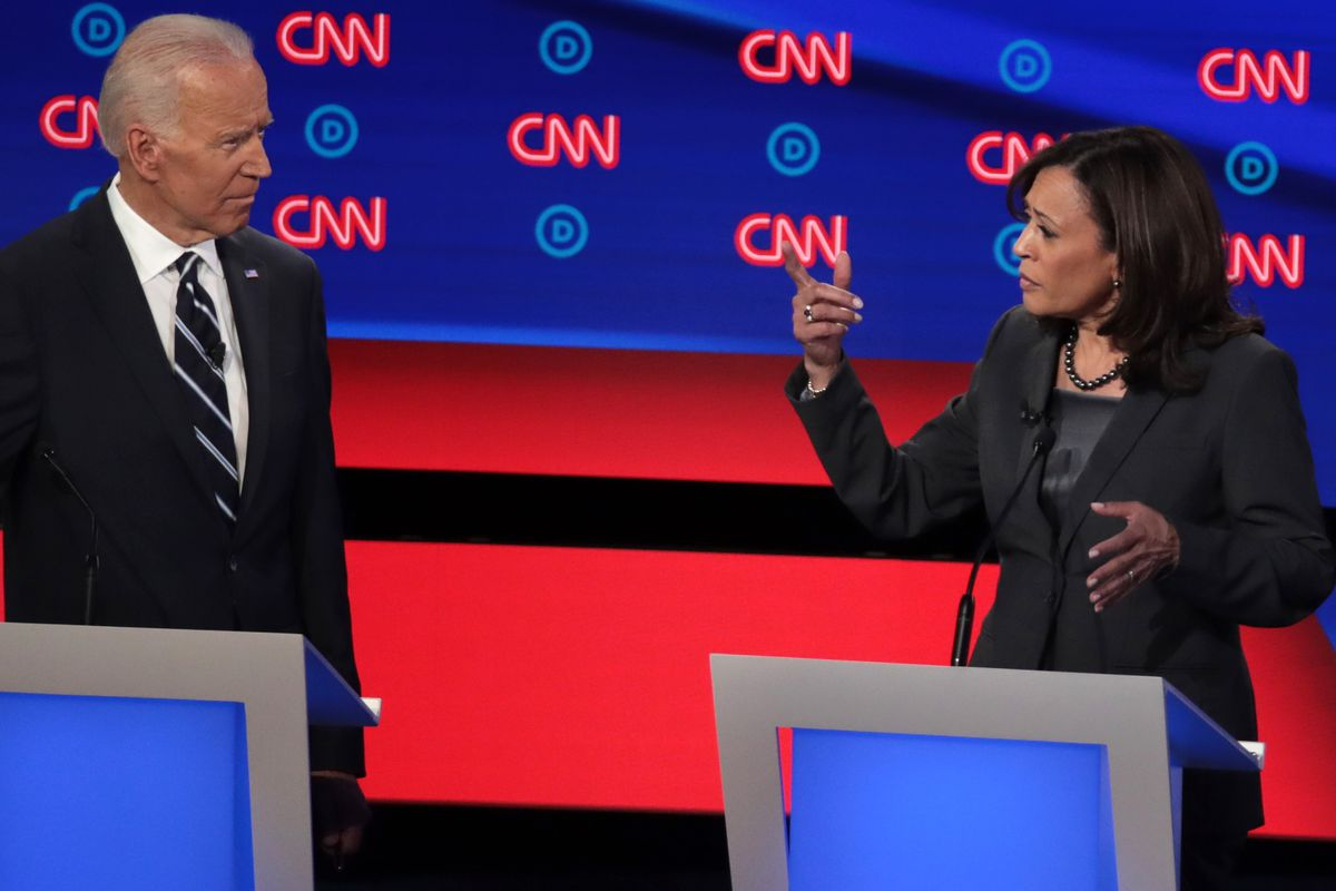 Joe Biden and Kamala Harris addressing one another on the Democratic debate stage from behind podiums.