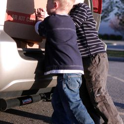 Adam and Judy Moore's sons load a box of food into the back of their parent's van. The family delivers meals to homebound seniors together once a month.