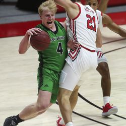 Utah Valley Wolverines guard Trey Woodbury (4) gets fouled by Utah Utes forward Riley Battin (21) during a game at the Huntsman Center in Salt Lake City on Tuesday, Dec. 15, 2020.