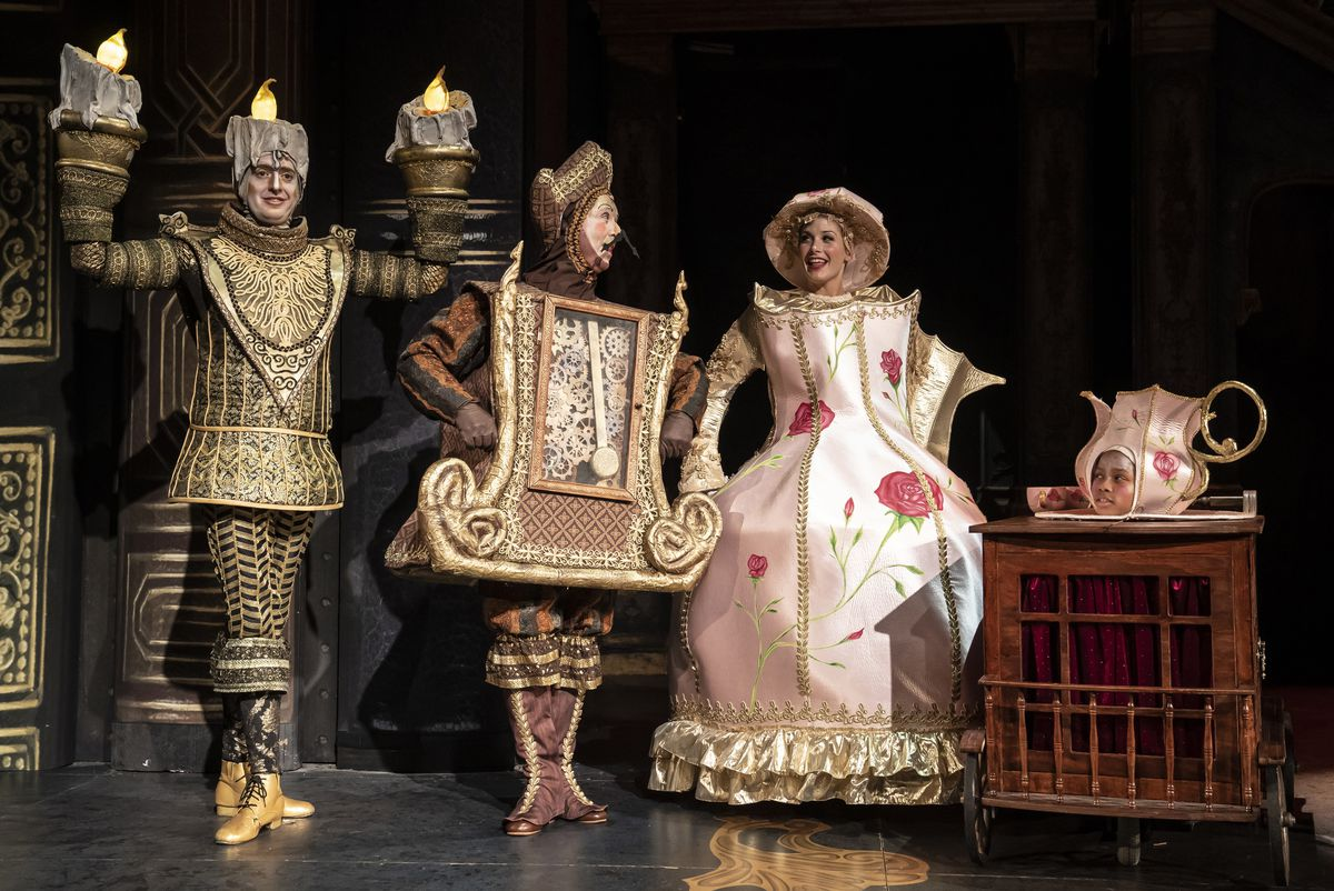 """Jackson Evans (left) as Lumiere, George Keating as Cogsworth, Jennie Sophia as Mrs. Potts and Izzie Rose as Chip in a scene from Paramount Theatre's new staging of Disney's """"Beauty and the Beast."""""""