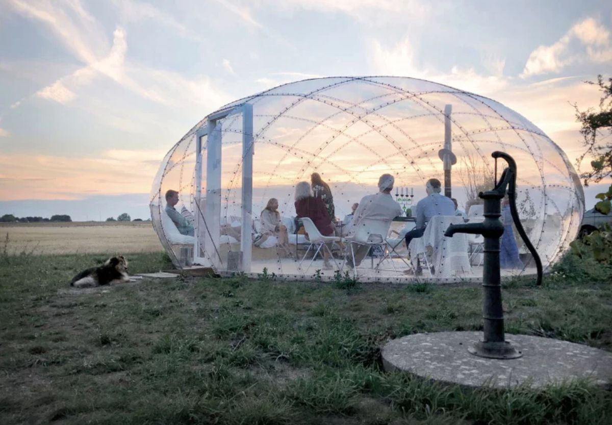 People sitting inside of transparent dome at dusk