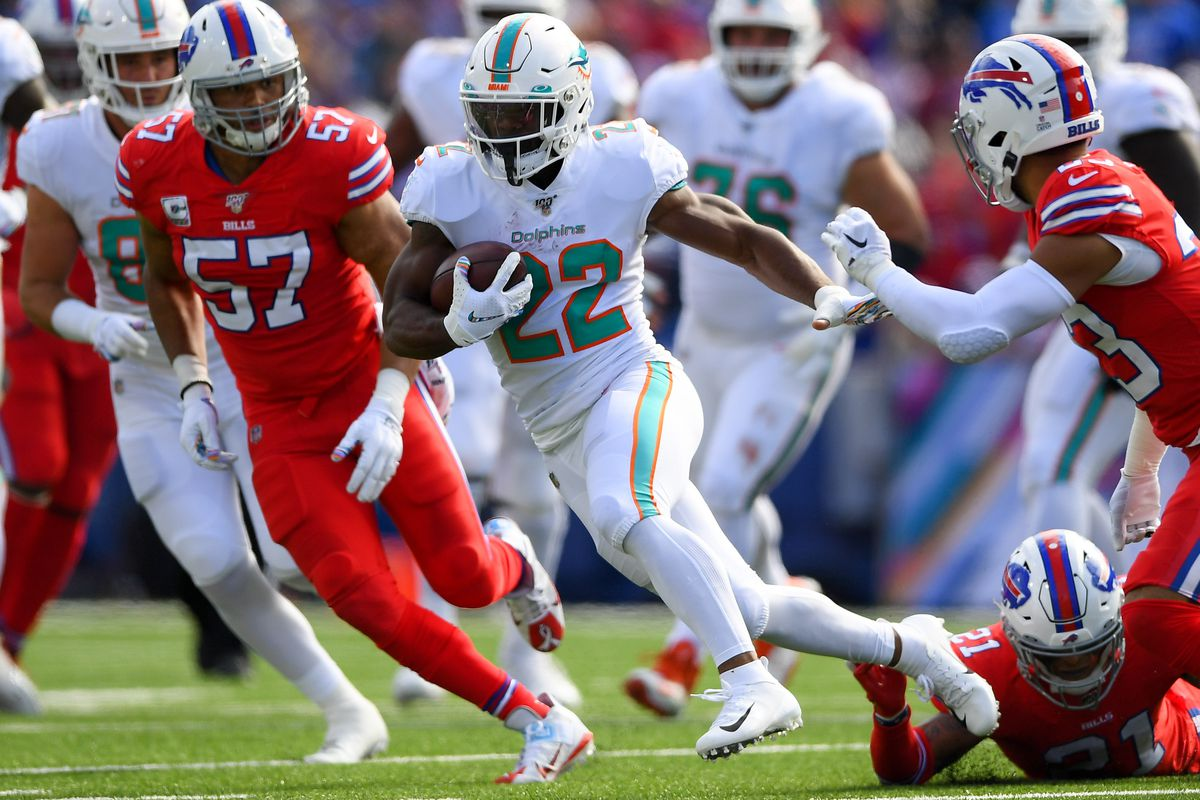 Miami Dolphins running back Mark Walton runs with the ball in front of Buffalo Bills outside linebacker Lorenzo Alexander during the first quarter at New Era Field.