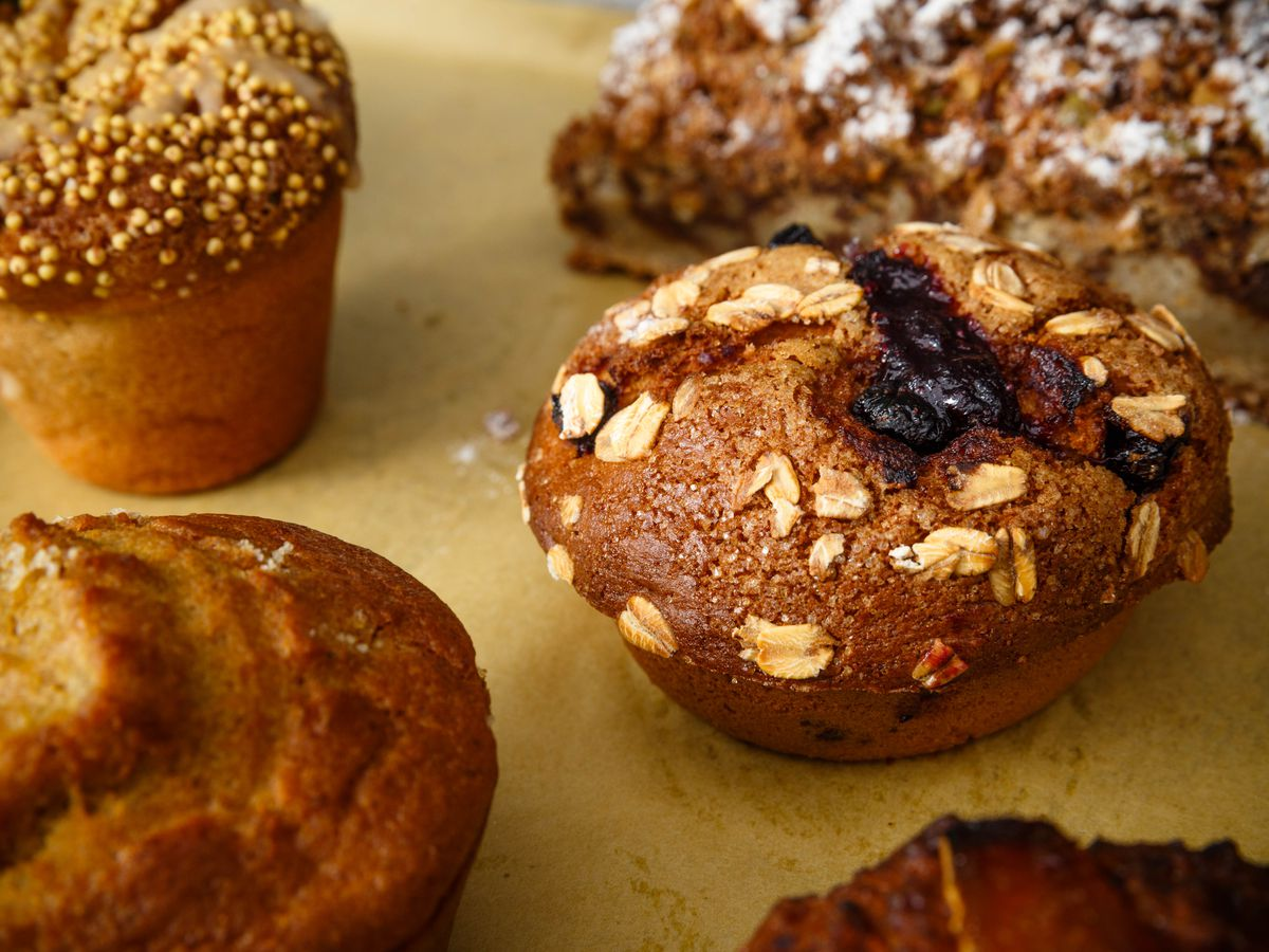 A photograph of a tray of baked goods, including a blueberry muffin topped with oats, a piece of coffee cake, and other pastries