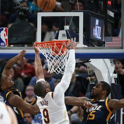 Cleveland Cavaliers guard Dwyane Wade (9) can't make the basket under pressure from Utah Jazz guard Donovan Mitchell (45) and forward Derrick Favors (15) at Vivint Arena in Salt Lake City on Saturday, Dec. 30, 2017.