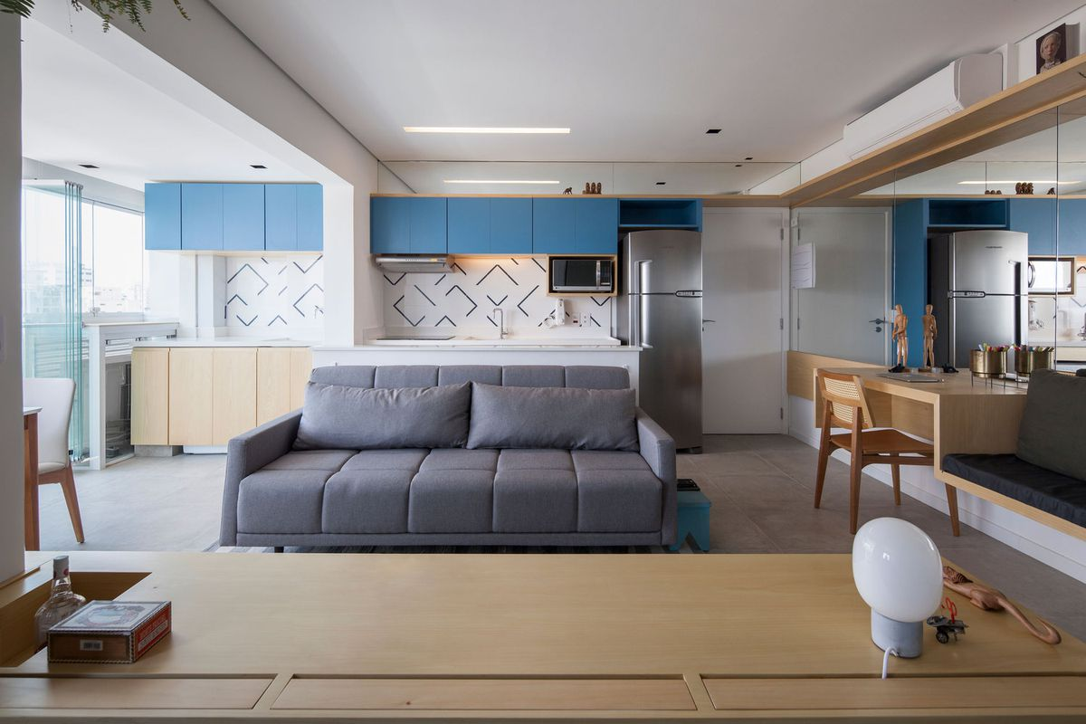 The Living Room Is Separated From Kitchen By A Low Wall And Contains Long Gray Couch Overlooking Computer Monitor Desk Bench Are Built Into