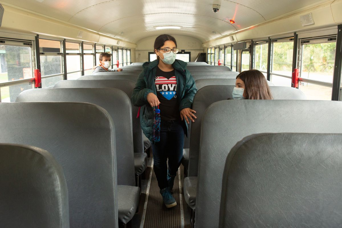 """Two fifth graders sit on opposite sides of a school bus while one girl, wearing glasses and a mask and a black T-shirt emblazoned with a red-and-blue heart saying """"LOVE"""" and carrying an umbrella, walks toward the back of the bus."""