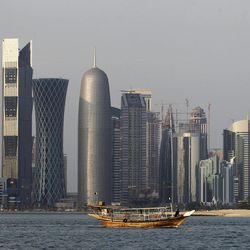 FILE - In this Thursday Jan. 6, 2011 file photo, a traditional dhow floats in the Corniche Bay of Doha, Qatar, with tall buildings of the financial district in the background. Qatar, now facing a diplomatic crisis with other Arab nations, is a small country with a big history of turmoil and coups as it became one of the world's top suppliers of natural gas and now plans to host the 2022 FIFA World Cup.