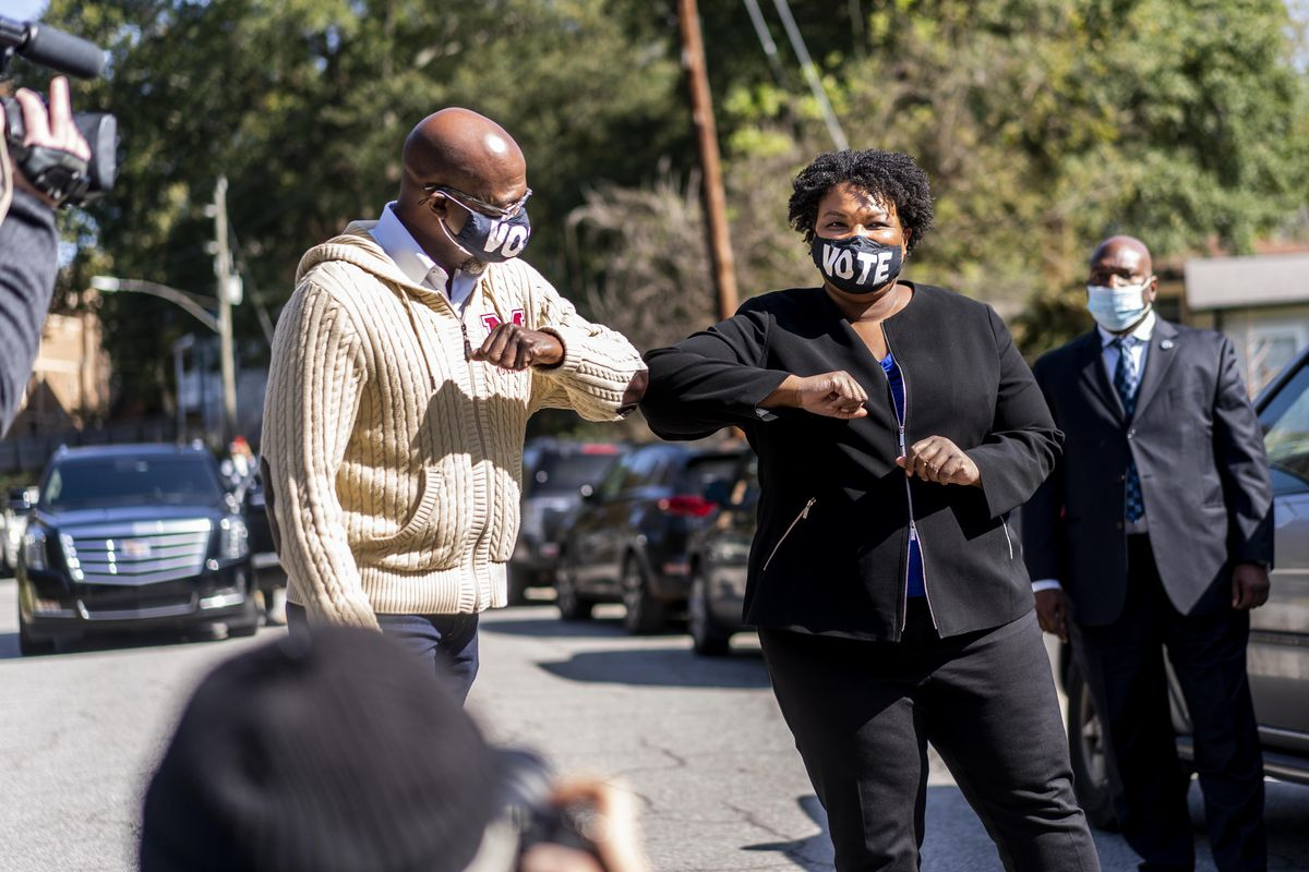 Senate candidate Raphael Warnock bumps elbows with voting rights activist Stacey Abrams while standing outside on an Atlanta street.