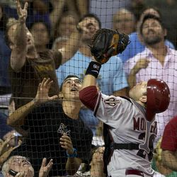 Arizona Diamondbacks catcher Miguel Montero, right, chases a ball to the net as fans look to catch it during the fifth inning of their baseball game against the San Diego Padres Friday, Sept. 7, 2012, in San Diego.