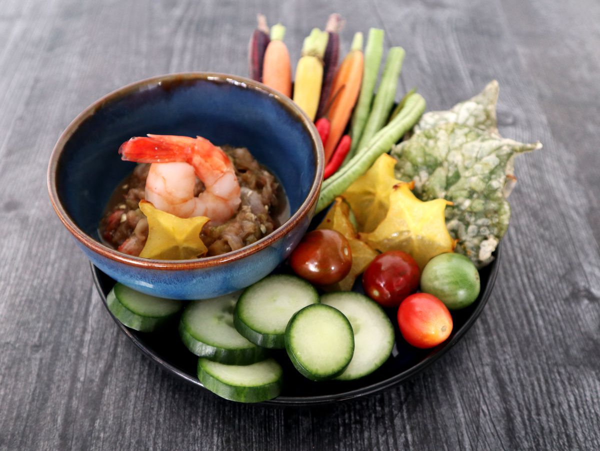 A plate of colorful vegetables and starfruit with a bowl of shrimp and chili relish to the side.