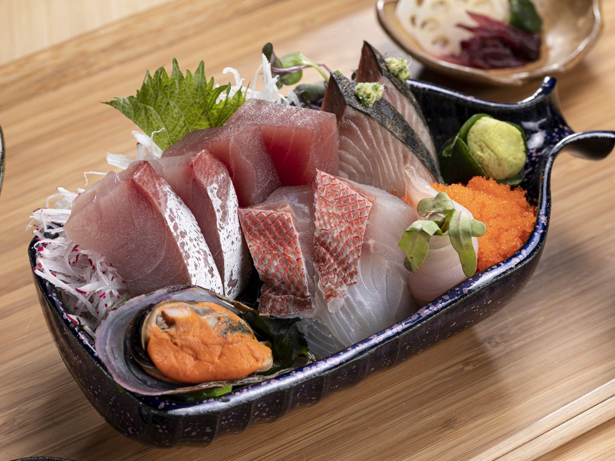 A small dish overflows with slices of various fish, a mussel, clump of roe, and mound of wasabi, on a wooden tray with other small plates blurred but visible nearby