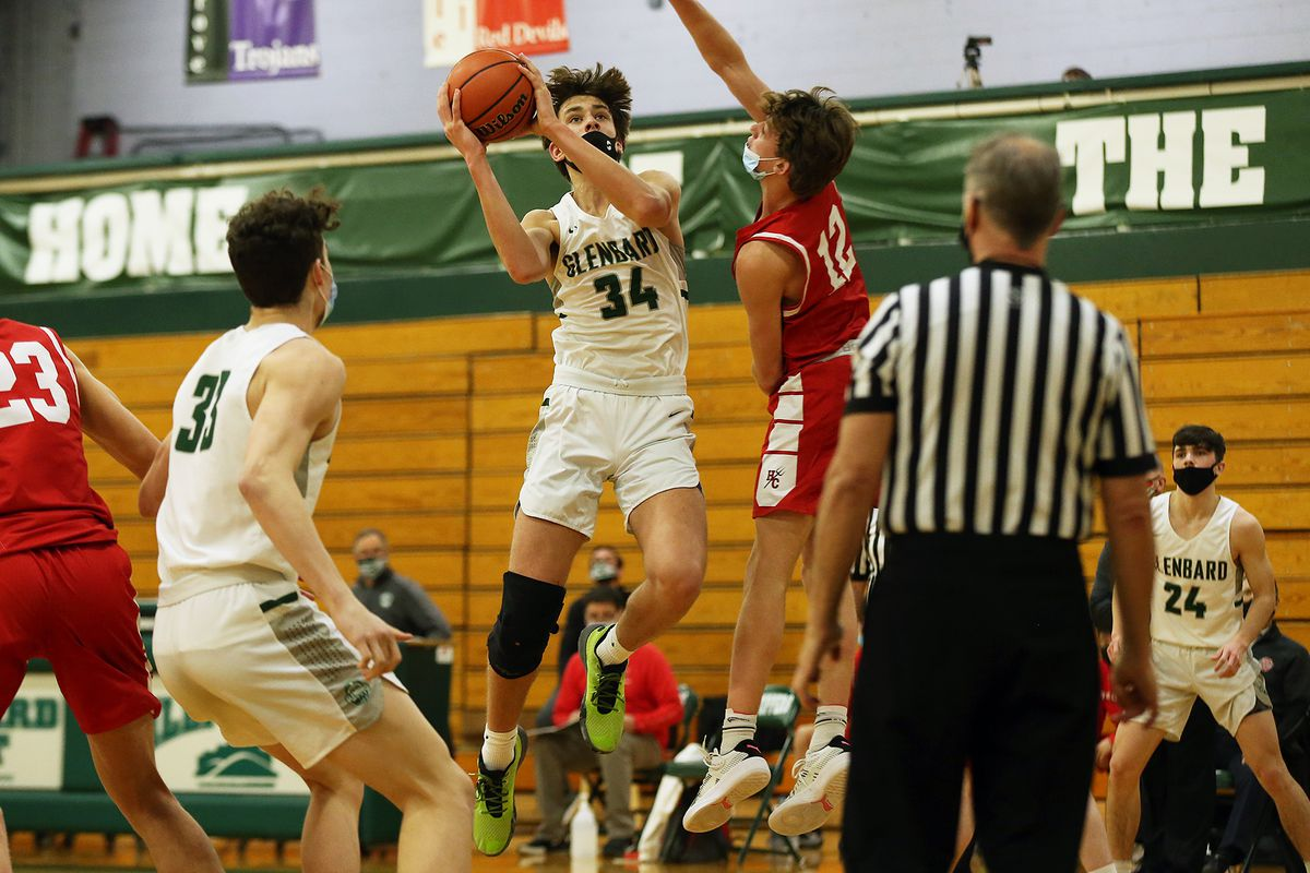 Glenbard West's Braden Huff (34) switches the ball to his right hand for a shot against Hinsdale Central.