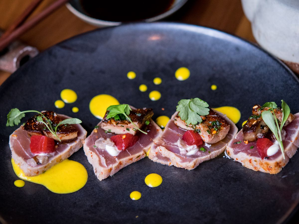 Overhead view of a fancy sashimi dish —four raw slices of tuna topped with seared foie gras and herbs. The tuna is on a dark blue plate, and a bright yellow sauce dots the plate artfully.