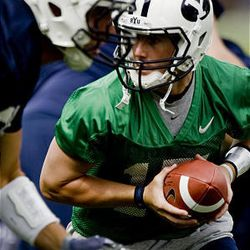 Cougar quarterback Max Hall gets ready to hand the ball off during practice at the BYU outdoor practice field in Provo Saturday. It was the Cougars' first day of fall camp.