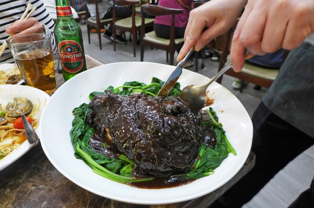 A giant black hump of pork on a nest of greens.