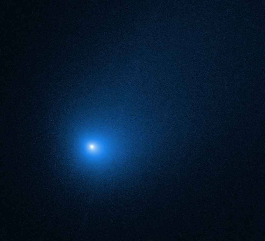 The comet appears as a glowing blue dot in this hubble space telescope image.