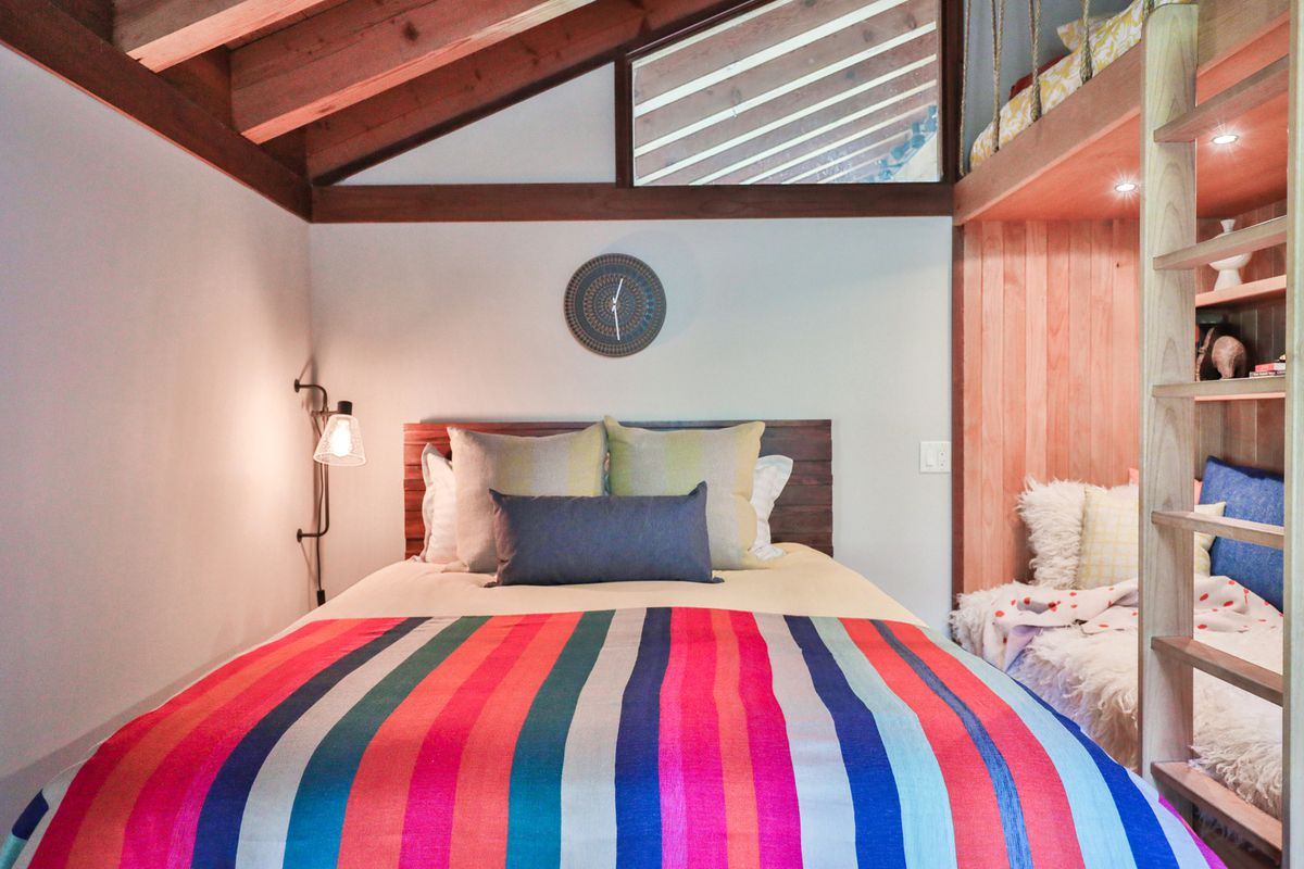 A bed with bright red, blue, and white vertical stripped comforter.