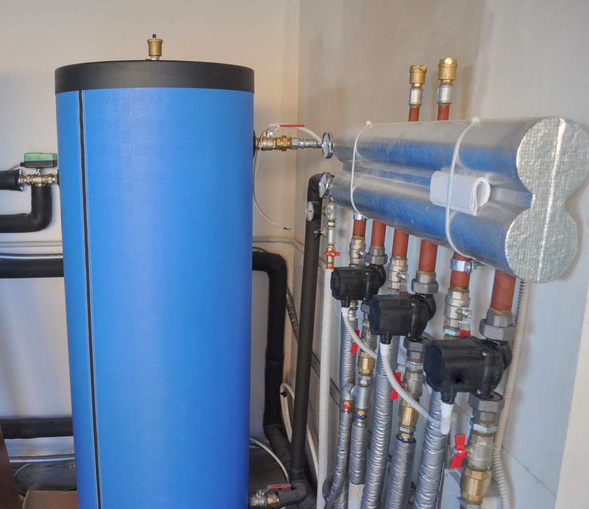 A blue geothermal heat pump in the interior of a home near silver pipes.