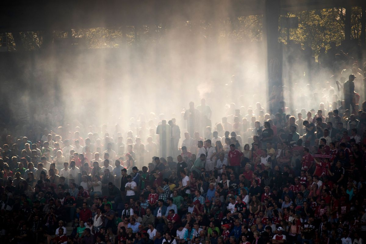 TOPSHOT - The sun cuts through the haze of flares hanging in the stand during the German first division Bundesliga football match between Hannover 96 vs Bayern Munich in Hanover, central Germany, on April 21, 2018.